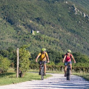 Couple cycling with rental e-bikes near Vipava old town, Slovenia.