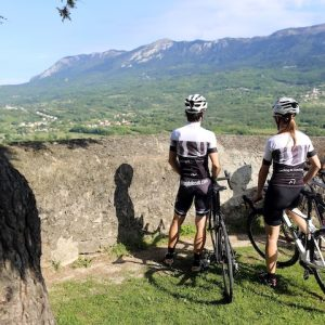 Group of cycling friends enjoying the view over the Vipava Valley during a road cycling trip.